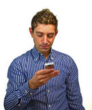 Attractive young man texting on cell phone. Good looking guy sending or reading text message on his mobile phone Royalty Free Stock Photos