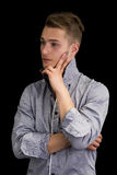 Attractive young man thinking, looking away with hand on his chin Stock Photos