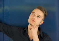 Attractive young man thinking, looking up with hand on his chin Royalty Free Stock Image