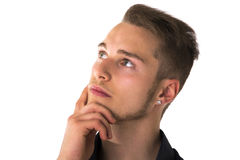Attractive young man thinking, looking up with hand on his chin Royalty Free Stock Photos