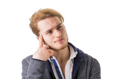 Attractive young man thinking, looking up with hand on his chin Stock Photos
