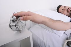Man turning off alarm clock. Attractive young man turning off the alarm clock. Indoors Royalty Free Stock Photography