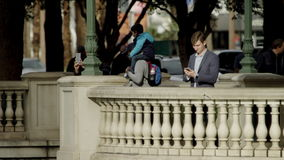 Attractive young man is typing a text message on his smartphone while standing on a Vegas sidewalk. Handsome young man is standing on a sidewalk in Las Vegas stock video footage