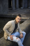 Attractive young man in urban setting, sitting on marble Royalty Free Stock Photos