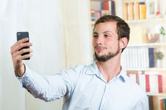Attractive young man using cell phone to take a Stock Photography