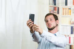 Attractive young man using cell phone to take a Stock Images