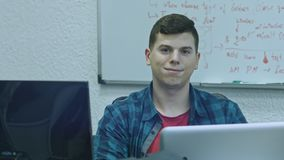 Attractive young man using computer at his working place. Office worker smiling and looking at camera.  stock video