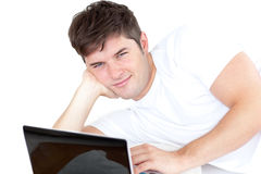 Attractive young man using his computer lying down Stock Photography