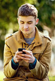 Attractive young man using a mobile phone Royalty Free Stock Photos