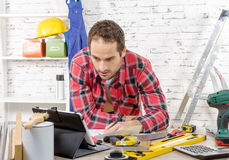 Attractive young man using the tablet for DIY Royalty Free Stock Photography