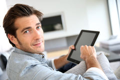 Attractive young man using tablet at home Stock Image
