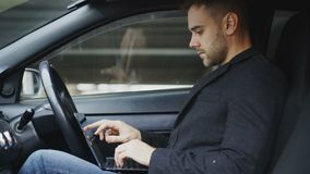Attractive young man using tablet laptop computer while sitting inside his car outdoors. Attractive young businessman using tablet laptop computer while sitting stock footage