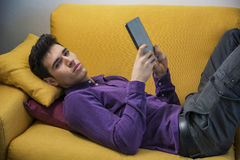 Attractive young man using tablet PC while laying Stock Photo