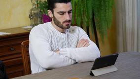 Young man using tablet PC to watch video or movie. Attractive young man using tablet PC to watch video or movie, while sitting at table at home stock video footage