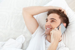 Attractive young man is using telephone for Royalty Free Stock Image
