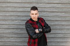 Attractive young man in a vintage plaid jacket with a stylish hairstyle in a t-shirt with a clock poses near a wooden wall. On a spring day. Fashionable serious royalty free stock images