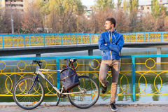 Attractive young man waiting for a friend. In a park leaning against colorful railings with folded arms and his bicycle beside him Royalty Free Stock Photo