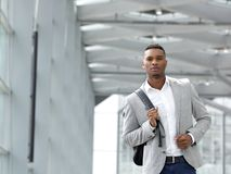 Attractive young man walking with bag Royalty Free Stock Images