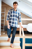 Attractive young man walking barefoot on stairs at home Stock Image