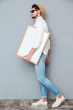 Attractive young man walking and holding blank white board Royalty Free Stock Photo