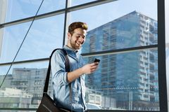 Attractive young man walking and looking at mobile phone Stock Image