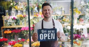 Attractive young man wearing apron holding open sign in flower store smiling. Looking at camera. Small business, happy employees and modern youth concept stock video footage