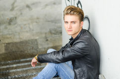 Attractive young man wearing black leather jacket. And jeans sitting on stairs Stock Photo