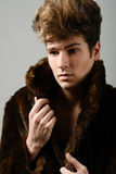 Attractive young man wearing fur coat with modern hairstyle Stock Images