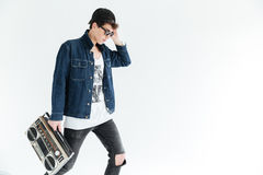 Attractive young man wearing glasses holding boombox. Picture of attractive young man wearing glasses standing  over white background and holding boombox Stock Photos