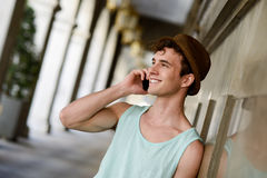 Attractive young man wearing hat talking on the mobile phone Stock Images