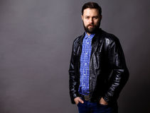 Attractive Young Man Wearing Leather Jacket on gray Royalty Free Stock Image