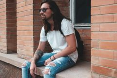 Attractive young man wearing sunglasses. And long hair relaxing in urban background. Sunglasses male model with long hair and tattoos on hand Stock Photo