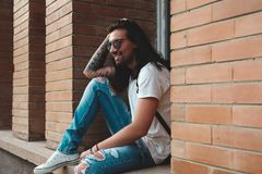 Attractive young man wearing sunglasses. And long hair relaxing in urban background. Sunglasses male model with long hair and tattoos on hand Stock Image