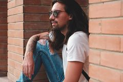 Attractive young man wearing sunglasses. And long hair relaxing in urban background. Sunglasses male model with long hair and tattoos on hand Royalty Free Stock Photos