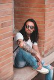 Attractive young man wearing sunglasses. And long hair relaxing in urban background sitting with bent leg. Sunglasses male model with long hair and tattoos on Stock Images