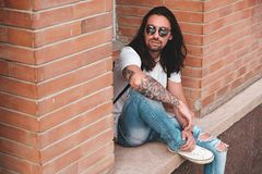 Attractive young man wearing sunglasses with tattoos. Attractive young man wearing sunglasses and long hair relaxing in urban background sitting with bent leg Royalty Free Stock Images