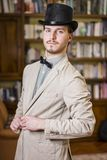Attractive young man wearing top hat and bow tie. Looking at camera. Indoors shot Royalty Free Stock Photography
