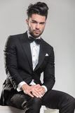 Attractive young man wearing tuxedo sitting Stock Image
