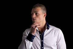 Attractive young man white shirt, hand on his chin Royalty Free Stock Photography