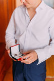 Attractive young man in white shirt holding stylish red black box with cufflinks and tie clip while dressing at hotel room Royalty Free Stock Photography