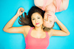 Attractive young man and woman lying head to head. Attractive young men and women lying on their backs head to head with their faces close together in pink stock photography