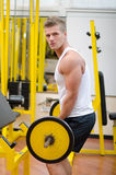 Attractive young man working out with barbell at gym Royalty Free Stock Image
