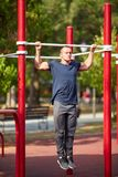 Fantastic young man doing push-ups on crossbars on a blurred background. Strength concept. royalty free stock photography