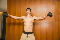 Attractive young man working out with dumbbells at Stock Photo