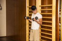 Attractive young man working out with dumbbells at Royalty Free Stock Images