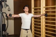 Attractive young man working out with dumbbells at Stock Image