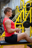 Attractive young man working out on gym equipment Royalty Free Stock Images
