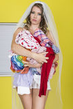 Attractive Young Married Woman Holding Dirty Washing Laundry. Beautiful Young Married Woman Carrying Laundry, standing against yellow background with white stock photos