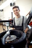 An attractive young mechanic is smiling while working at a car workshop stock images