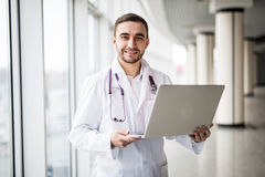 Attractive young medical worker using laptop. Isolated on white background royalty free stock photography